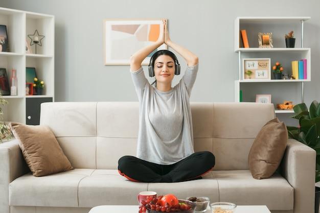 リビングルームのコーヒーテーブルの後ろのソファに座ってヨガをしているヘッドフォンを身に着けている若い女の子を喜ばせる