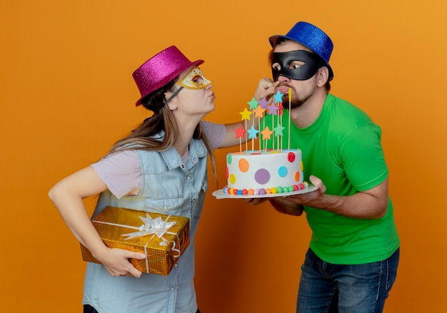 Pleased young girl wearing pink hat and masquerade eye mask holds gift box and holds cheek of joyful handsome man in blue hat wearing masquerade eye mask holding birthday cake