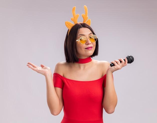 Felice giovane ragazza che indossa corna di renna archetto e bicchieri tenendo il microfono guardando la telecamera che mostra la mano vuota isolata su sfondo bianco