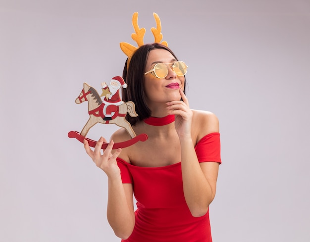 Pleased young girl wearing reindeer antlers headband and glasses holding santa on rocking horse figurine touching chin looking up isolated on white background with copy space