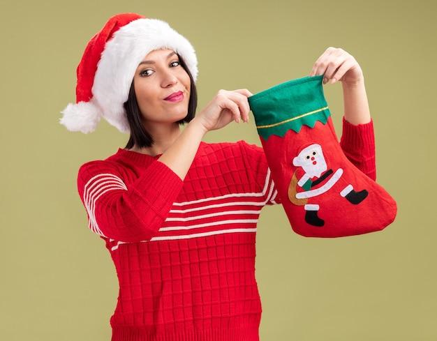 Довольная молодая девушка в шляпе санта-клауса держит рождественский чулок на оливково-зеленой стене