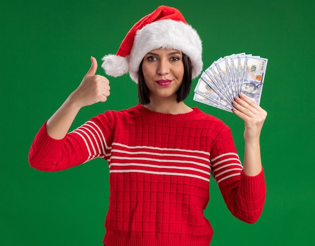 Pleased young girl wearing santa hat holding money  showing thumb up isolated on green wall