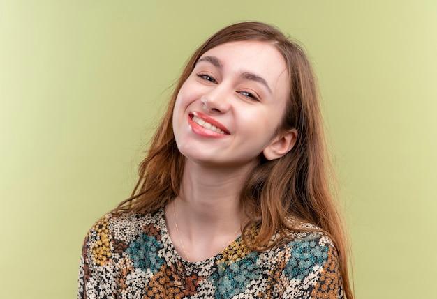カメラをポジティブで幸せな笑顔で見てカラフルなドレスを着て長い髪の若い女の子