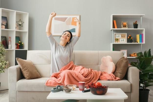Довольная молодая девушка, завернутая в плед, протягивая руку, сидя на диване за журнальным столиком в гостиной