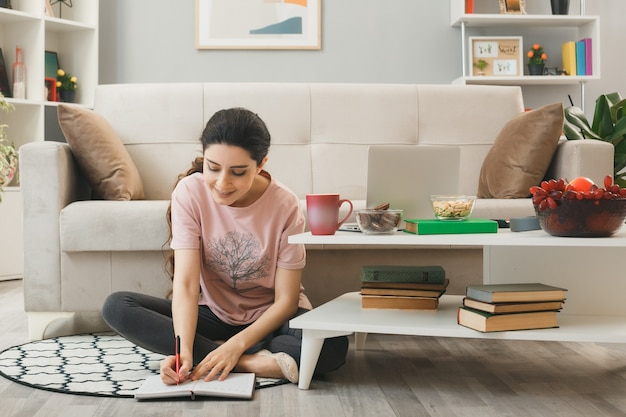 기쁘게 어린 소녀는 거실에 있는 커피 테이블 뒤에 바닥에 앉아 있는 공책에 글을 씁니다.