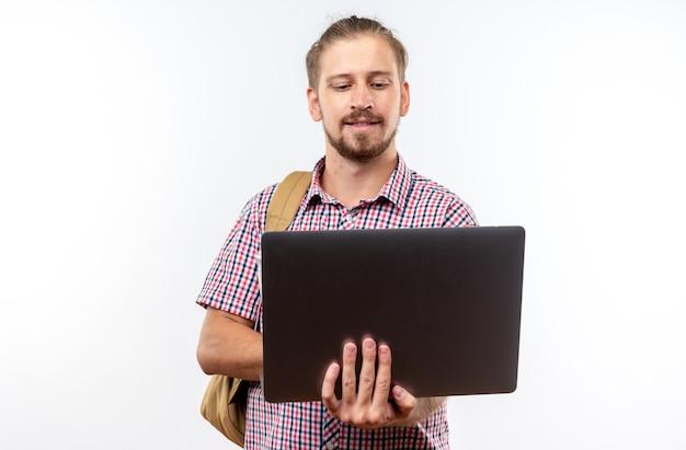白い壁に隔離されたバックパックを保持し、使用されたラップトップを身に着けている若い男の学生を喜ばせる