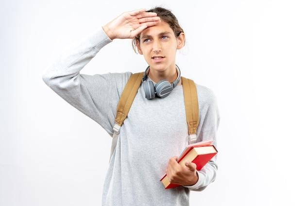 白い壁に隔離された額に手を置いて本を保持している首にヘッドフォンでバックパックを身に着けている若い男の学生を喜ばせる