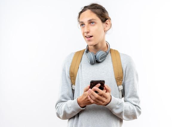 白い壁に分離された電話を保持している首にヘッドフォンとバックパックを身に着けている若い男の学生を喜ばせる