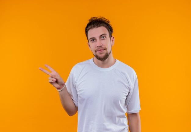 격리 된 오렌지 배경에 평화 제스처를 보여주는 흰색 티셔츠를 입고 기쁘게 젊은 남자