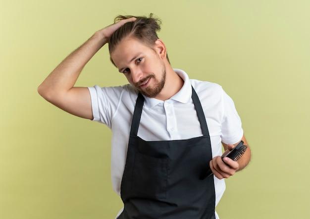 彼の髪に触れ、オリーブグリーンの壁に隔離された櫛を保持している若いハンサムな床屋を喜ば