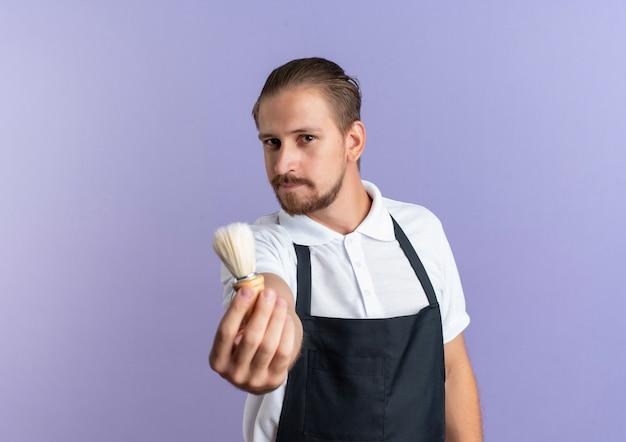 舒展剃须刷的高兴的年轻英俊的理发师佩带的制服往紫色墙壁隔绝的前面