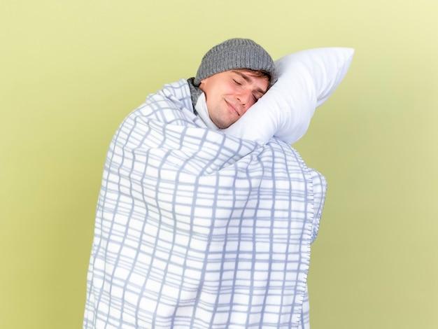 Довольный молодой красивый блондин больной мужчина в зимней шапке и шарфе, завернутый в плед, держит подушку, положив на нее голову с закрытыми глазами, изолированными на оливково-зеленом фоне