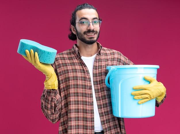 Довольный молодой красивый уборщик в футболке и перчатках держит ведро с губкой, изолированное на розовой стене