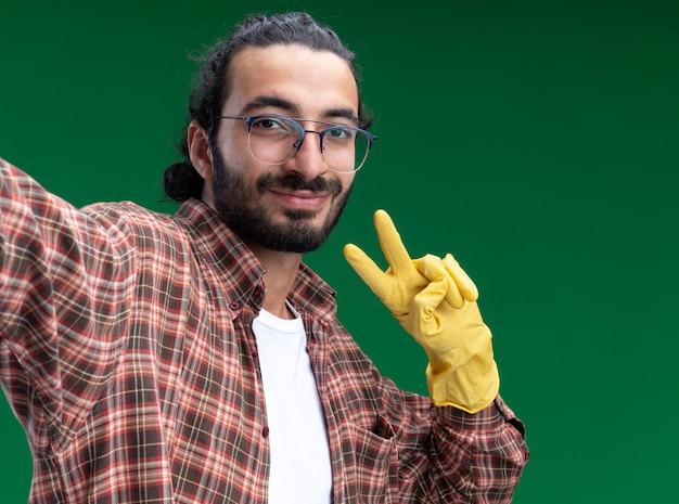 Soddisfatto giovane bel ragazzo delle pulizie che indossa t-shirt e guanti che tengono la parte anteriore che mostra il gesto di pace isolato sulla parete verde