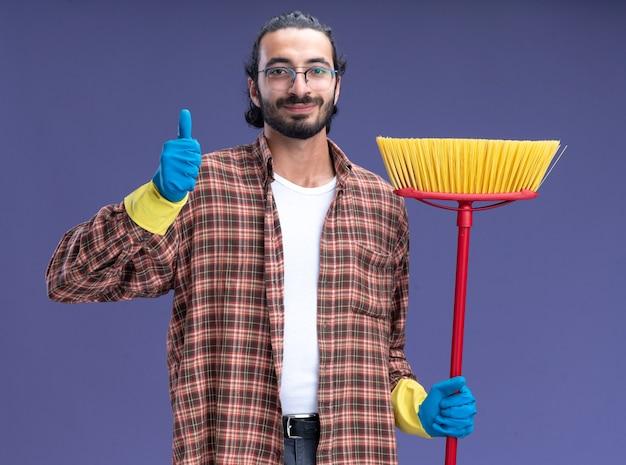 Soddisfatto giovane bel ragazzo delle pulizie che indossa t-shirt e guanti in possesso di mop che mostra il pollice in alto isolato sulla parete blu