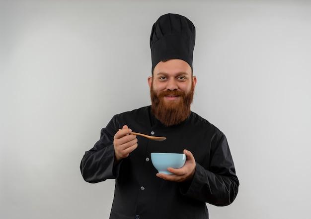 Soddisfatto giovane cuoco bello in ciotola e cucchiaio della holding dell'uniforme del cuoco unico isolati su spazio bianco