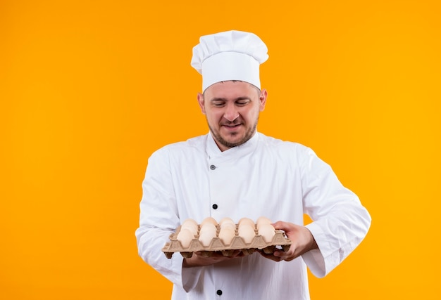 Pleased young handsome cook in chef uniform holding and looking at carton of eggs isolated on orange space