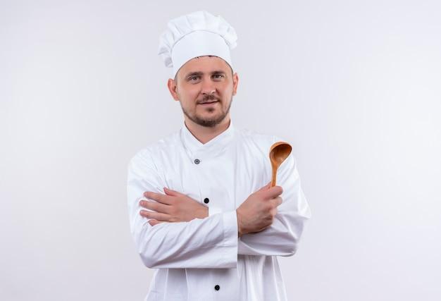 Soddisfatto giovane cuoco bello in cucchiaio uniforme della holding del cuoco unico che sta con la posizione chiusa isolata su spazio bianco