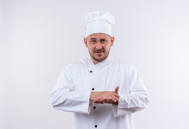 Felice giovane cuoco bello in uniforme da chef tenendo le mani insieme isolato su uno spazio bianco
