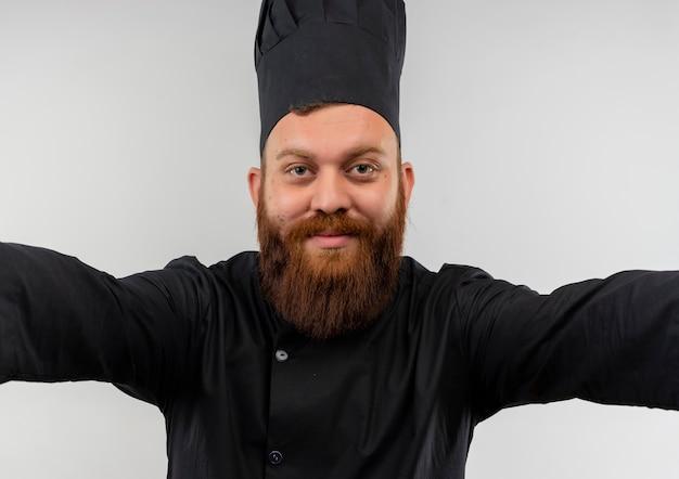 Felice giovane cuoco bello in uniforme del cuoco unico che osserva con le braccia aperte isolate su uno spazio bianco