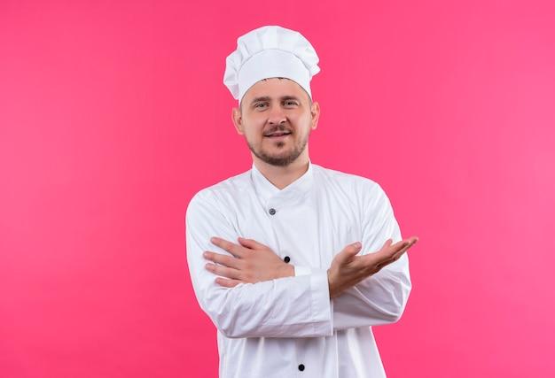 Felice giovane cuoco bello in uniforme da chef che mostra la mano vuota e mettendo la mano sul braccio isolato sullo spazio rosa