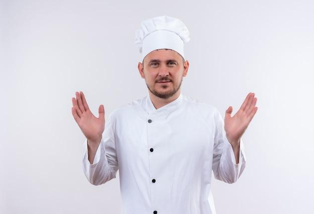 Felice giovane cuoco bello in uniforme del cuoco unico che mostra le mani vuote isolate su uno spazio bianco