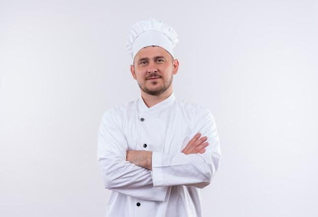 Felice giovane cuoco bello in uniforme da chef in piedi con la postura chiusa isolata su uno spazio bianco