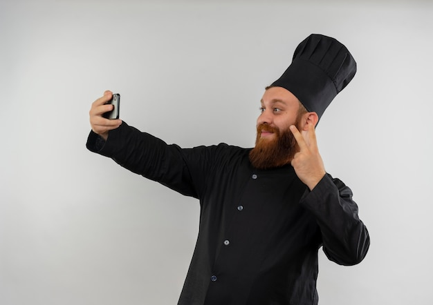ピースサインをして、白いスペースで隔離されたselfieを取るシェフの制服を着た若いハンサムな料理人を喜ばせる