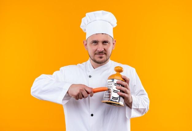 オレンジ色のスペースで隔離おろし金とシェフの制服格子ニンジンで若いハンサムな料理人を喜ば