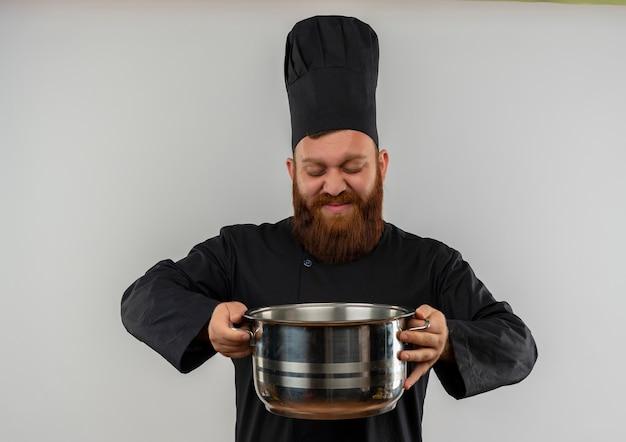 白いスペースで隔離の鍋を保持し、見てシェフの制服を着た若いハンサムな料理人を喜ばせる