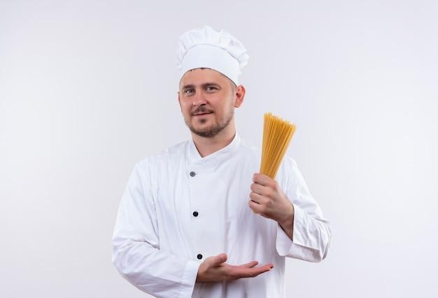 白いスペースで隔離のスパゲッティパスタを保持し、指しているシェフの制服を着た若いハンサムな料理人を喜ばせる