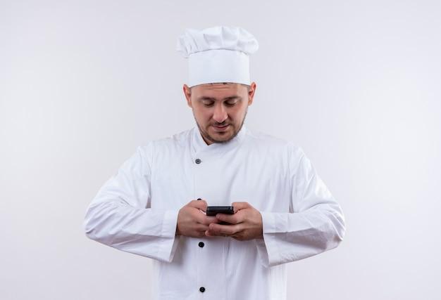 白いスペースで隔離の携帯電話を保持し、使用してシェフの制服を着た若いハンサムな料理人を喜ばせる