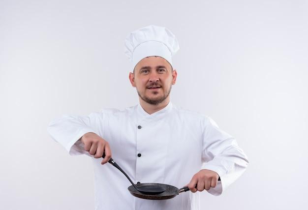 孤立した白いスペースでフライパンとおたまを保持しているシェフの制服を着た若いハンサムな料理人を喜ばせる
