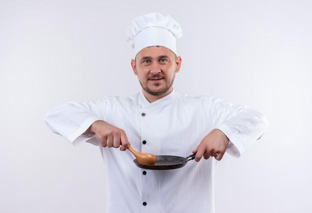 白いスペースで隔離のフライパンとスプーンを保持しているシェフの制服を着た若いハンサムな料理人を喜ばせる