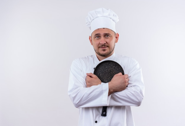 白いスペースで隔離のフライパンを保持しているシェフの制服を着た若いハンサムな料理人を喜ばせる