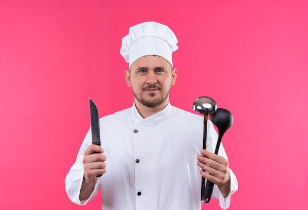 ピンクのスペースで隔離のナイフと鍋を保持しているシェフの制服を着た若いハンサムな料理人を喜ばせる