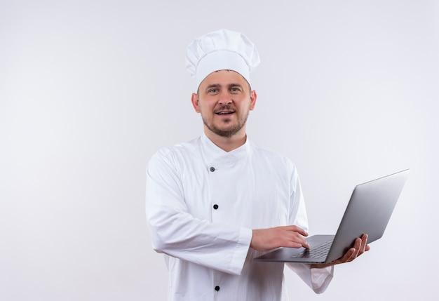 Довольный молодой красивый повар в униформе шеф-повара держит ноутбук на изолированном белом пространстве