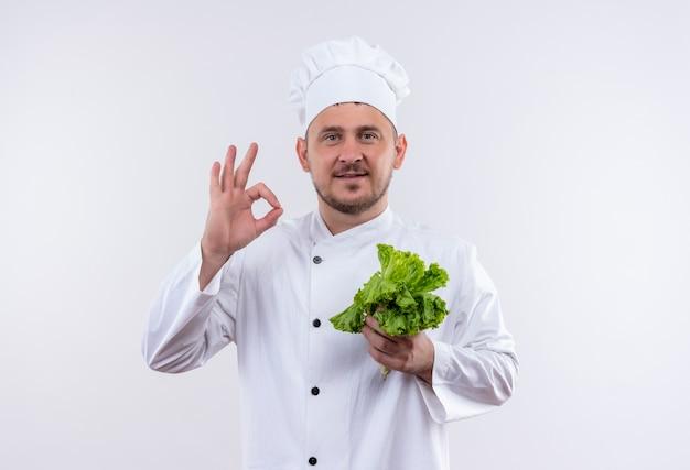 レタスを保持し、白いスペースで隔離のokサインをしているシェフの制服を着た若いハンサムな料理人を喜ばせる