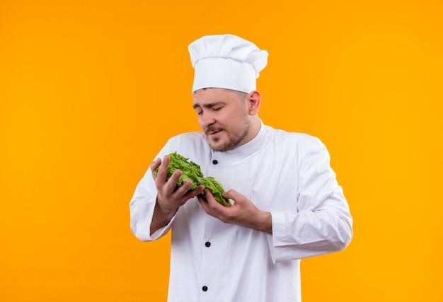 オレンジ色の空間に隔離された目を閉じてレタスを保持しているシェフの制服を着た若いハンサムな料理人を喜ばせる