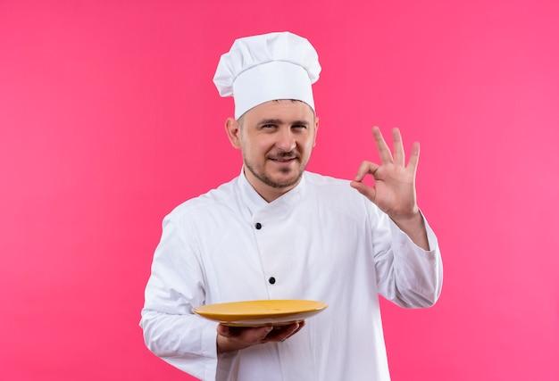 シェフの制服のプレートを保持し、ピンクのスペースに分離されたokサインをやって満足している若いハンサムな料理人