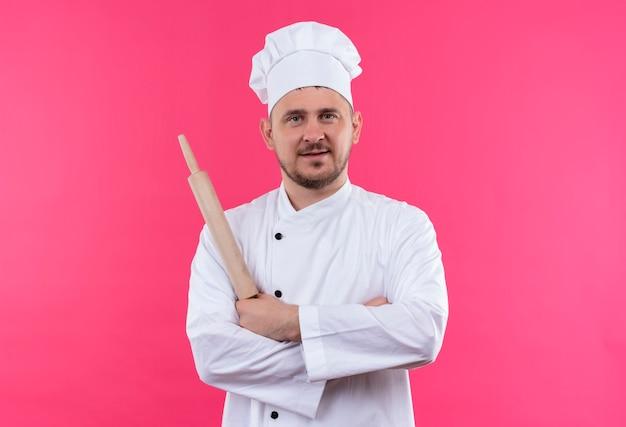 Довольный молодой красивый повар в униформе шеф-повара держит скалку и стоит в закрытой позе, изолированной на розовом пространстве