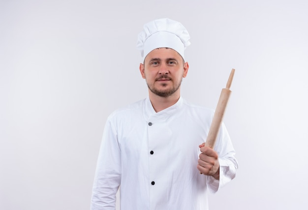 白いスペースに分離された麺棒を保持しているシェフの制服を着た若いハンサムな料理人を喜ばせる
