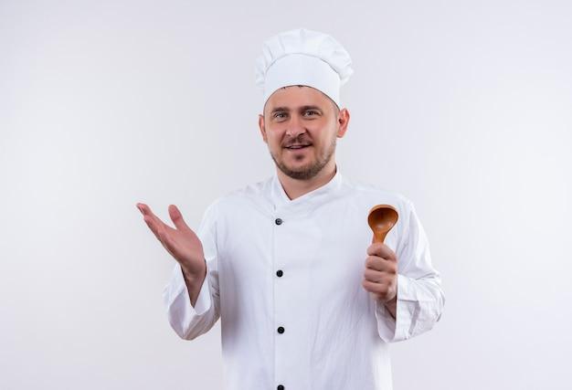 スプーンを保持し、白いスペースで隔離の空の手を示すシェフの制服で若いハンサムな料理人を喜ば