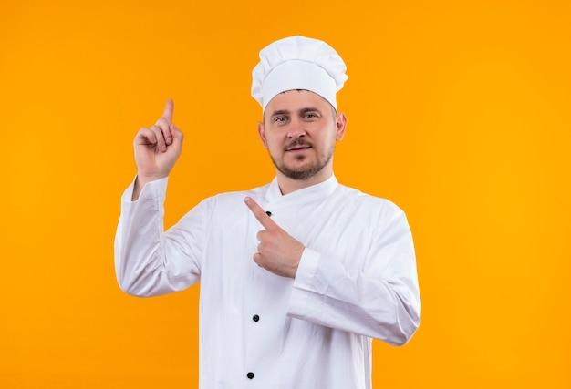 オレンジ色のスペースに隔離された上向きのシェフの制服を着た若いハンサムな料理人を喜ばせる