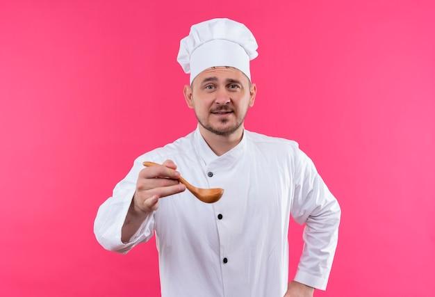 ピンクのスペースで隔離のスプーンを伸ばしてシェフの制服を着た若いハンサムな料理人を喜ばせる