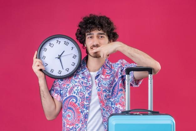 Soddisfatto giovane viaggiatore riccio bello uomo che tiene l'orologio puntato su di esso e mettendo il braccio sulla valigia su uno spazio rosa isolato