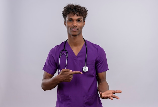 A pleased young handsome dark-skinned doctor with curly hair wearing violet uniform with stethoscope  while pointing with index finger