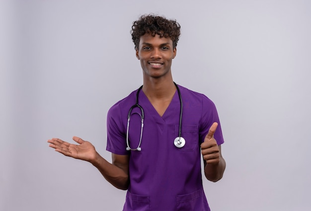 A pleased young handsome dark-skinned doctor with curly hair wearing violet uniform with stethoscope  with thumbs up