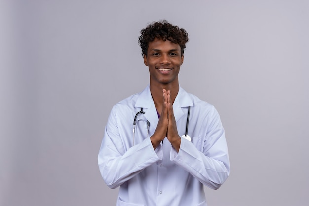 A pleased young handsome dark-skinned doctor with curly hair wearing white coat with stethoscope showing thankful gesture with hands