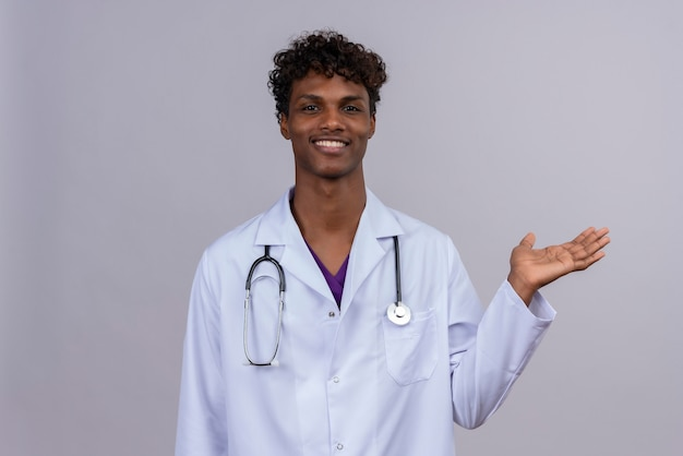 A pleased young handsome dark-skinned doctor with curly hair wearing white coat with stethoscope smiling and raising hand